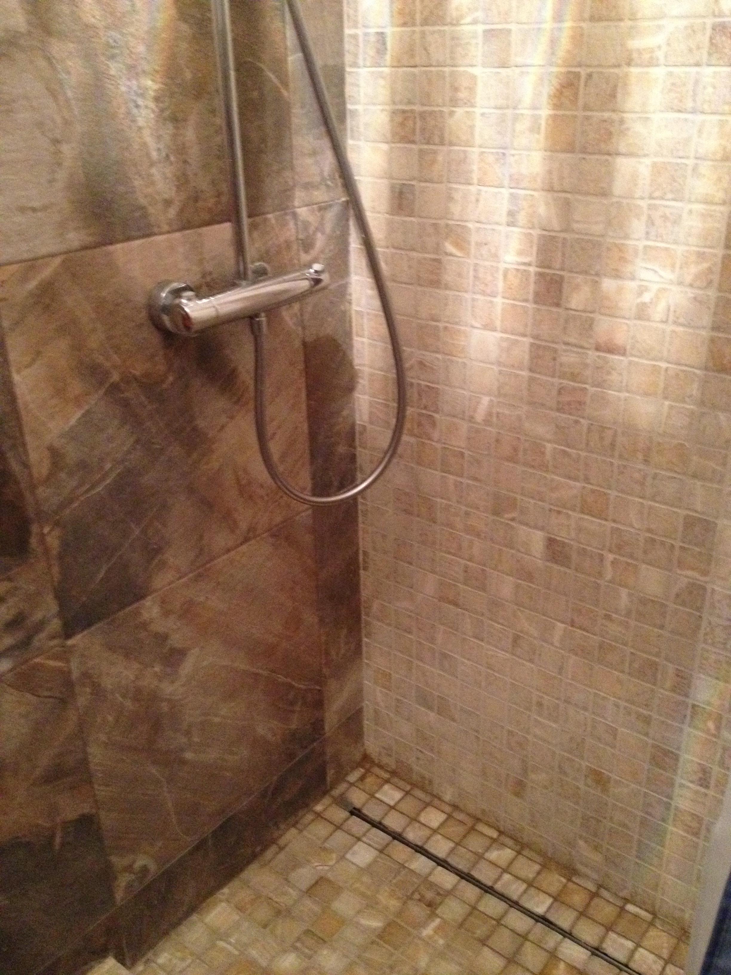 Крупноформатная керамогранитная плитка 60 х 60 см в сочетании с мраморной мозаикой — удачное решение для маленького санузла.