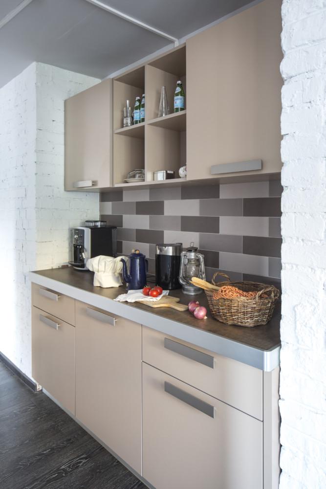 Кухня в мини-пространстве в переговорной. Фартук на кухне коричневого цвета в стиле лофт.