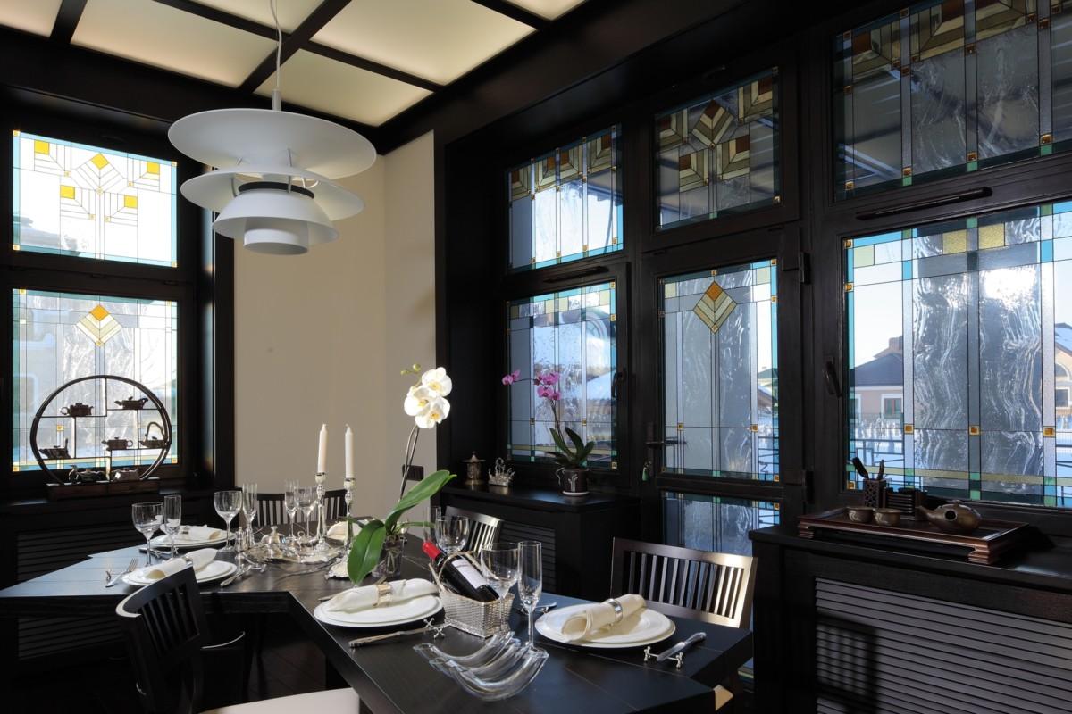 Логичным продолжением гостиной стал интерьер столовой, выдержанный в той же цветовой гамме и полный удивительных дизайнерских находок. Так, стоит обратить внимание на сложный многогранный обеденный стол, на удивительной красоты рифовый аквариум, за которым скрывается кухня, или на матовый стеклянный потолок, разлинованный на квадраты тёмным деревом и подсвеченный изнутри.