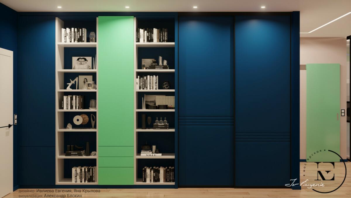 Прекрасное решение сделать в холле большую библиотеку и шкаф с системой хранения. Давайте рассмотрим этот шедевр. Открытые полки для книг и аксессуаров чередуются с закрытыми колонками и шкафом. Ярко-синие дверцы фасада подобраны в тон стены. Средняя дверца нежно-мятного цвета хорошо гармонирует с дверным полотном в основном холле. Точечные потолочные светильники хорошо подсвечивают всю панораму корпусной мебели.