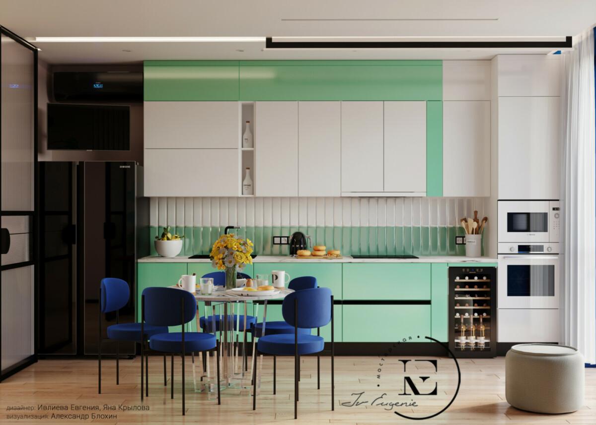 Столовая группа состоит из круглого стола с мраморной столешницей и акриловым основанием.  Синие стулья выглядят очень стильно и ярко. В кухонном гарнитуре нижние модули выполнены в нежно-мятном цвете, а верхние с белоснежным фасадом. Встроенный винный шкаф удобно расположен рядом с колонкой для бытовой техники. Черный двухстворчатый холодильник и такой же цвету кондиционер хорошо гармонируют с темными вставками на фасаде гарнитура. «Кухонный фартук» выполнен из двухцвентной плитки узкой вытянутой формы.