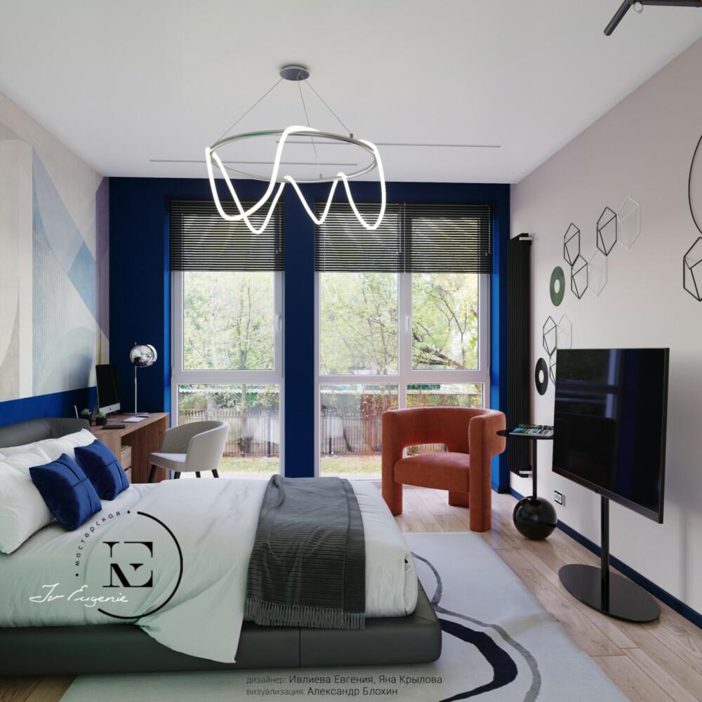 С этого ракурса хорошо виден дизайнерский прием - покраска стены с панорамным окном в ярко-синий цвет. Таким же оттенком выполнена отделка нижней части изголовья кровати и стола. За счет  игры с цветом кажется, что поток дневного света увеличился в несколько раз. Уникальное кресло кирпичного цвета наполняет комнату уютом и нежностью.